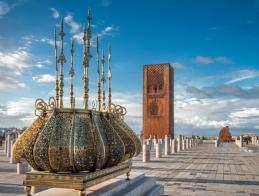 islamic_muslim_religious_architecture._traditional_golden_decorations_with_the_emblem_of_morocco._tour_hassan_tower_in_a_background_with_stone_columns_rabat_morocco